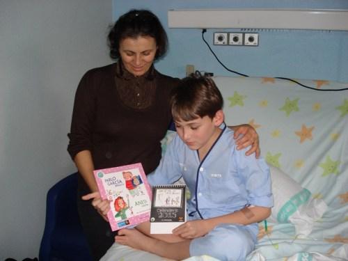 Niño ingresado y su madre con el libro Día Discapacidad